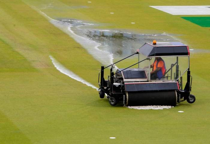 Ground staff removes the water from the ground using a super sopper as the rain stops the semi-final match between india and new zealand