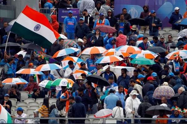Fans wait for the game to resume as the rain interrupts the semi-final match between india and new zealand