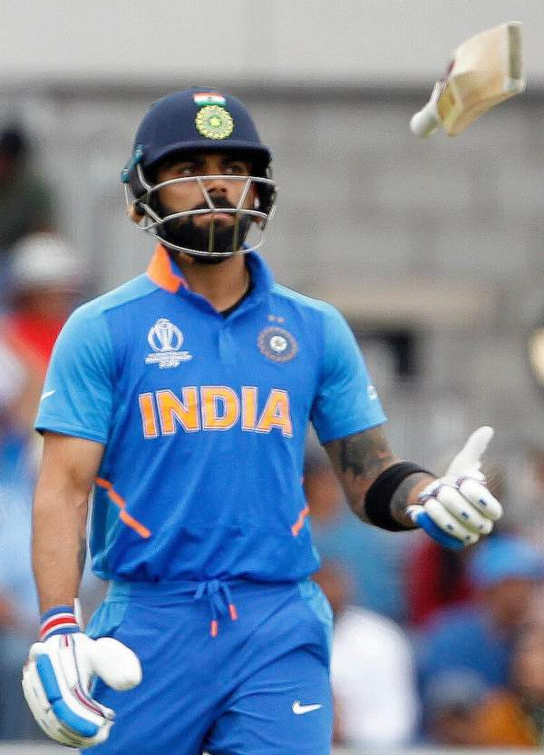 Indian captain virat kohli leaves the ground after being dismissed during the semi final match against new zealand