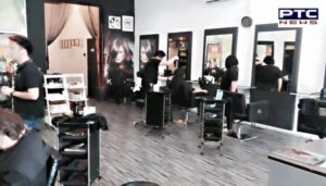 Salon owner cuts customers' hair with gold scissors