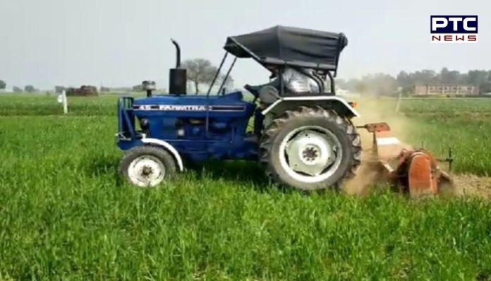 Farmer drives a tractor on a wheat crop in protest of agricultural laws